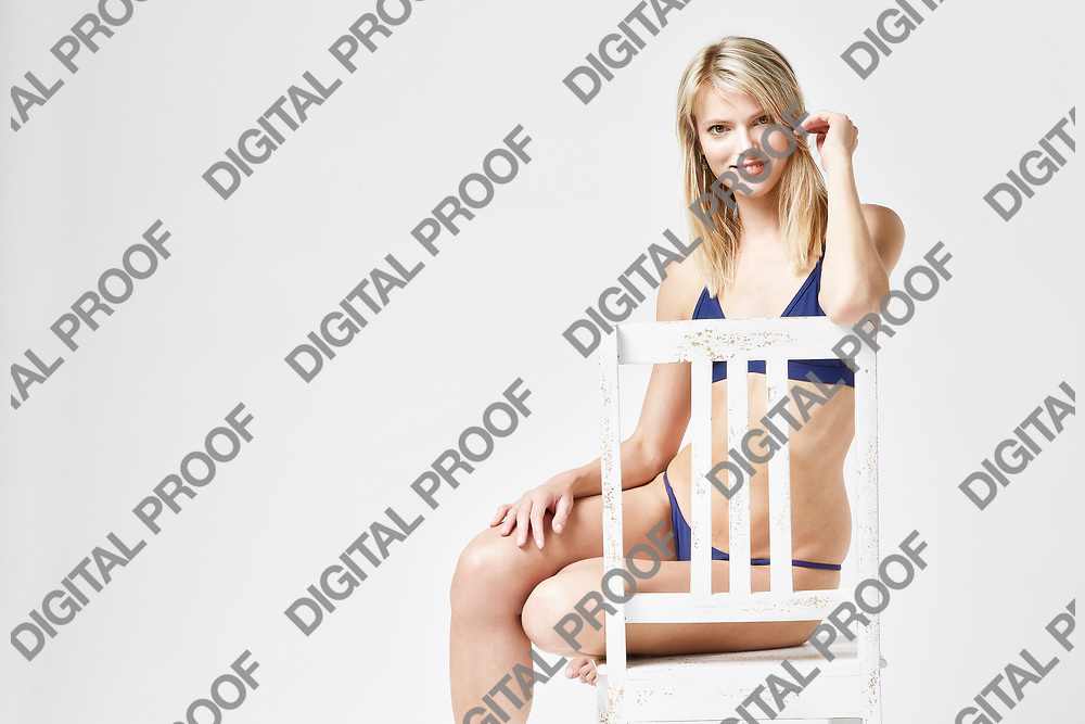 Portrait of a happy woman seated and smiling in underwear at studio with a white background