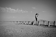 Black and white photo of a nude woman with old pier pilings in the Great Salt Lake, Utah