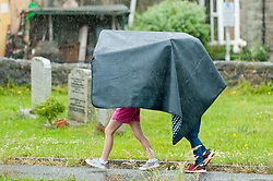 © Licensed to London News Pictures. 16/06/2020. Builth Wells, Powys, Wales, UK. Children walk through a churchyard under a sheet during a thunderstorm in Builth Wells, Powys, UK. Thunderstorms and heavy rain hit Powys, Wales, UK. Photo credit: Graham M. Lawrence/LNP