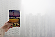 The Lonely Planet, a detailed guide to Shanghai is held against tall high rise accommodation blocks in a veil of air pollution that cloaks the city