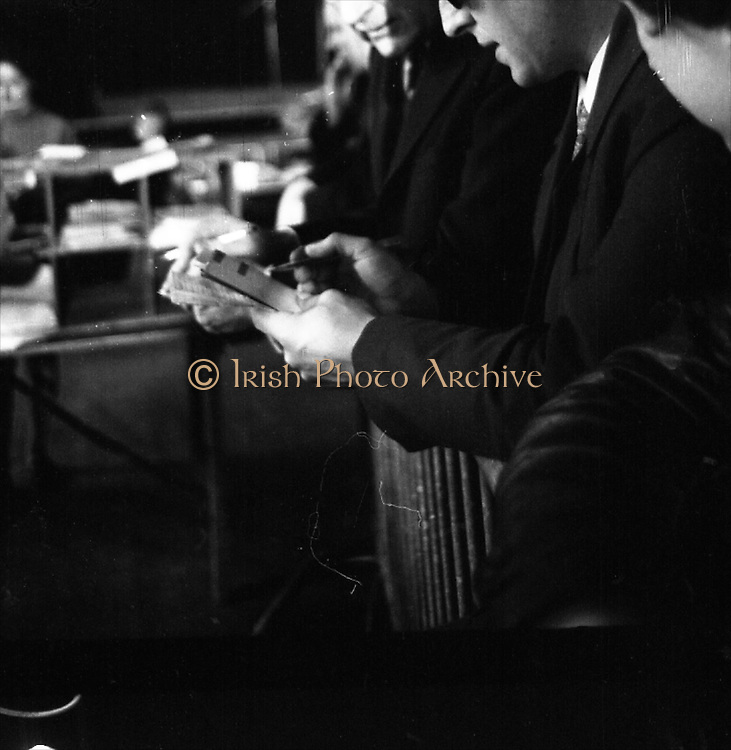 Mr Liam Cosgrave,Leader of Fine Gael,at Vote Count. (E48)1973..01.03.1971..03.01.1973..1st March 1973..As the ballot boxes were opened in Dun Laoghaire Town Hall, Mr Cosgrave and his supporters watched as the voting papers were piled high. The vote was as the result of an often hectic General Election campaign. Mr Cosgrave was hoping his party would garner enough votes to oust the sitting Fianna Fail Government which had held power for sixteen years...Picture of a tallyman,alongside Mr Liam Cosgrave, assessing the impact of the votes on the outcome of the general election.
