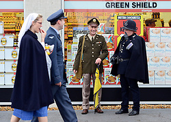 © Licensed to London News Pictures. 13/09/2013. Chichester, UK People in costume outside a period Tesco store. People enjoy the atmosphere at the 2013 Goodwood Revival. The event recreates the glorious days of motor racing and participants are encouraged to dress in period dress. The revival is the only event of its kind to be staged entirely in the nostalgic time capsule of the 1940s, 50s and 60s Photo credit : Stephen Simpson/LNP.