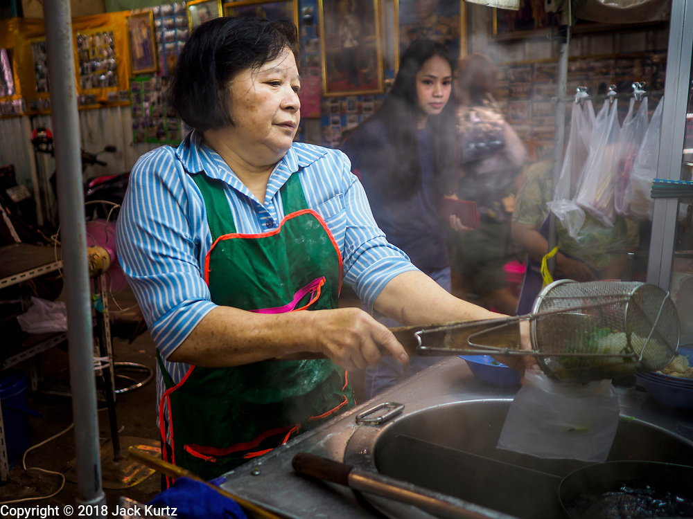 23 FEBRUARY 2018 - BANGKOK, THAILAND: A vendor prepares an order of take away soup for a customer at a soup stand in Pratunam Market. Pratunam Market was one of the largest clothing markets in Bangkok. New airconditioned markets, like Platinum and Palladium malls opened nearby, siphoning away customers. Now there are only a handful of merchants left in the market and Bangkok city officials have plans to shut the market and redevelop the land.     PHOTO BY JACK KURTZ