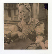 Portrait of an elder Hmong woman. The hilltribe female wears big silver earring and traditional dress outfit. Vietnam, Asia.