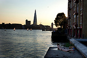Woman sunbathing by the River Thames in Wapping, London, UK. On a summer evening and as sailing boats pass by, this is a relaxing place to lie out reading.