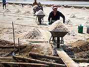 "28 MARCH 2014 - NA KHOK, SAMUT SAKHON, THAILAND:  Thai workers haul salt to a warehouse in Samut Sakhon province.Thai salt farmers south of Bangkok are experiencing a better than usual year this year because of the drought gripping Thailand. Some salt farmers say they could get an extra month of salt collection out of their fields because it has rained so little through the current dry season. Salt is normally collected from late February through May. Fields are flooded with sea water and salt is collected as the water evaporates. Last year, the salt season was shortened by more than a month because of unseasonable rains. The Thai government has warned farmers and consumers that 2014 may be a record dry year because an expected ""El Nino"" weather pattern will block rain in mainland Southeast Asia. Salt has traditionally been harvested in tidal basins along the coast southwest of Bangkok but industrial development in the area has reduced the amount of land available for commercial salt production and now salt is mainly harvested in a small parts of Samut Songkhram and Samut Sakhon provinces.   PHOTO BY JACK KURTZ"