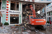Old China comes crashing down. A Daewoo digger knocks down one of the last remaining old buildings in the heart of Pudong, Shanghai's financial district. The 'Welcome' sign and Chinese lanterns in marked contrast to the ever present destruction of old Shanghai around the city.