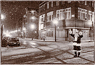 Santa waves to traffic from the center of Franklin Square in Middletown last night after appearing at the city's Holiday Tree Lighting ceremony. Snow started falling during the ceremony.<br /> Dec. 5, 2003.