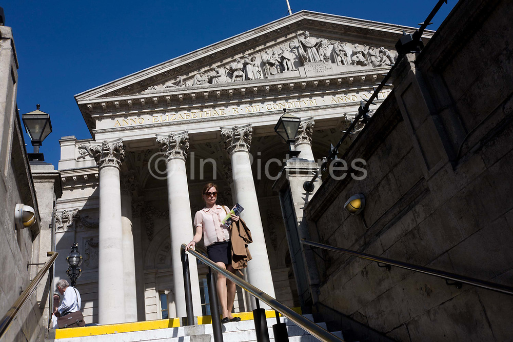 A commuter descend the steps from the bright daylight to the dark of the London Underground, before making her way home from Royal Exchange at Bank Triangle by tube. Behind her are the tall and solid Corinthian pillars of the 3rd Royal Exchange built in 1842 by Sir William Tite. She is about to descend underground to Bank tube (subway) station beneath the streets of the financial district, otherwise known as the Square Mile. The lady homeward in the afternoon, her commuting exodus shared by its daily working population of 311,000. This perspective of suggests a bank and its architecture looking powerful and influential in the UK's economy. The pillars give a sense of establishment, a scene of classic stability and strength.