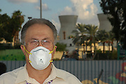 Israel, Haifa bay, A man wearing a protective mask at a protest against air pollution The oil refinery in the back ground