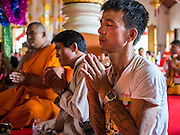 """04 APRIL 2015 - CHIANG MAI, CHIANG MAI, THAILAND:  A Tai (Shan) man prays at Wat Phra Singh during the Poi Song Long Festival in Chiang Mai. The Poi Sang Long Festival (also called Poy Sang Long) is an ordination ceremony for Tai (also and commonly called Shan, though they prefer Tai) boys in the Shan State of Myanmar (Burma) and in Shan communities in western Thailand. Most Tai boys go into the monastery as novice monks at some point between the ages of seven and fourteen. This year seven boys were ordained at the Poi Sang Long ceremony at Wat Pa Pao in Chiang Mai. Poy Song Long is Tai (Shan) for """"Festival of the Jewel (or Crystal) Sons.     PHOTO BY JACK KURTZ"""