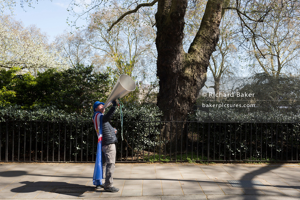 On the day that Prime Minister Theresa May returns to Brussels to negotiate an expected Brexit delay, the pro-EU activist Steve Bray shouts at a TV interview through his megaphone through the gates of parliament in Westminster, in London, England.