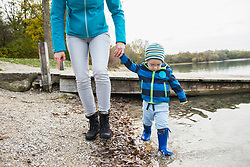 Mother and son walking hand in hand in front of jetty at shore of lake in autumn