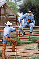 rear view of a cowboy while another cowboy on a fence looks off