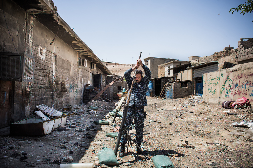 An Iraqi Federal Police officer prepares to fire a mortar towarads ISIS's position at the frontline in West Mosul.<br />