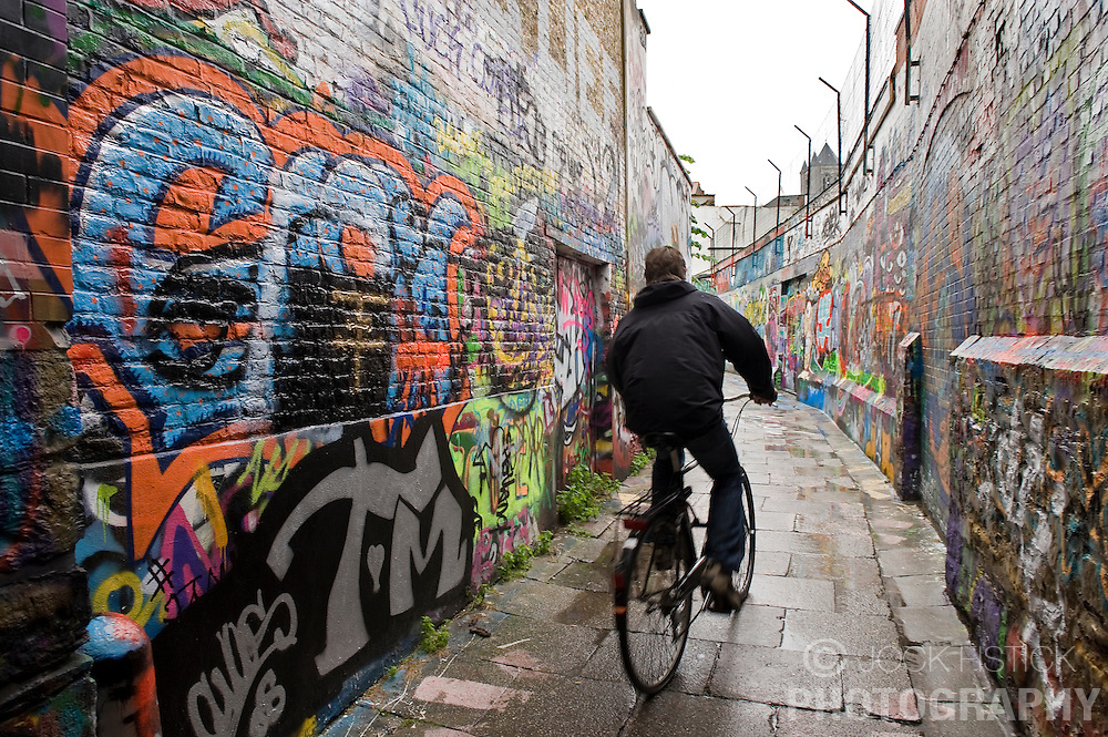 "A bicyclist rides down ""Graffiti Alley""  in Ghent, Belgium, on Friday, Sept. 12, 2008. The street, which is actually named Werregaran Straat, was made a safe zone for ""taggers"" to ply their art in an attempt to deter graffiti artists from vandalizing the city. (Photo © Jock Fistick)"