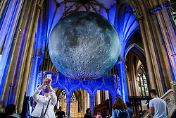 © Licensed to London News Pictures. 15/08/2021. Bristol, UK. A woman takes a selfie with Luke Jeram's Moon installation in Bristol Cathedral. Measuring seven metres in diameter, the Museum of the Moon features detailed NASA imagery of the lunar surface. At an approximate scale of 1:500,000 each centimetre of the internally lit spherical sculpture represents 5 km of the moon's surface. The Museum of the Moon  is open until 30 August 2021. Photo credit: Dinendra Haria/LNP