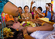"""TOOTH FILING IN BALI<br /> <br />  5am in a little village of south Bali, Indonesia. For two days the teens have prayed in a special place and are now ready for the tooth filing ceremony. The whole village combined the ceremony to reduce the high costs.<br />  The girls and even the boys have a make up session. The young people are dressed in gorgeous clothing and big headdresses that are rented for the celebration. The atmosphere looks more like a movie set than a religious celebration.  Balinese tooth-filing is an ancient tradition that predates Hinduism's arrival on the island in the 5th century BCE. Ancient tradition meets now the modern techniques with metal braces that have invaded Asia for years now.  The teeth of gods and spirits are always pointed and long. They are likened to those of ferocious evils, wild animals, or dogs. It's believed a Balinese may be denied entrance into heaven if the teeth are not filed because she might be mistaken for a wild creature.  The tooth filing ceremony starts in the temple with the mebyakala , a series of purification with holy water made by the big priest (pedanda' ) ceremony to """"cleanse"""" the teenagers before having their teeth filed   The aim of the ceremony is to symbolically """"cut down"""" on the six negative traits that are inherent in humans (like the 7 sins in Christianity) : lust, greed, wrath, pride, jealousy, and intoxication.  Tooth filing is a rite of passage into adulthood. The teens bow in front their parents and thanks them for everything they've since they were born. It is a very sequence full of emotions.  The teens show respect to her parents in front of the whole family and many end in tears. The teens have to go thru the ceremony when a boy's voice change or when the girls has her first menstruations.  Before the filing begins, the priest says superstitious sentences. A ruby ring that is believed to have huge power is used to protect the teen from the evil. The stone touches the teeth as the protection symb"""