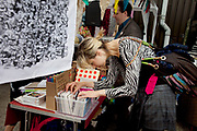 Flicking through art for sale. The Art Car Boot Fair in a car park just off Brick Lane in East London. This is an alternative art event where artists show their works and engage with the public. The Art Car Boot Fair was an idea that grew out of a desire to re-introduce some summer fun and frivolity into a thriving but increasingly commercial London art scene. The aim for the Art Car Boot Fair is to be a day when the artists let their hair down and for all-comers to engage with art in a totally informal way, and to pick up some real art bargains.