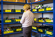 A female volunteer prepares an emergency food package at Wadebridge foodbank, North Cornwall, England, United Kingdom. The food bank is part of the Trussell Trust charity which provides assistance to individuals and families in crisis and living below the poverty line.
