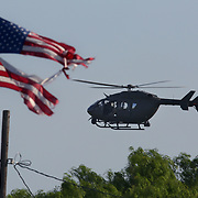 A U.S. Army helicopter hovers above a field just south of a home displaying a tattered U.S. flag Thursday, April 12, 2018, in La Joya, Texas. The helicopter is part of a recent inclusion of the Texas Army National Guard to boost border security. <br /> Photo by Nathan Lambrecht