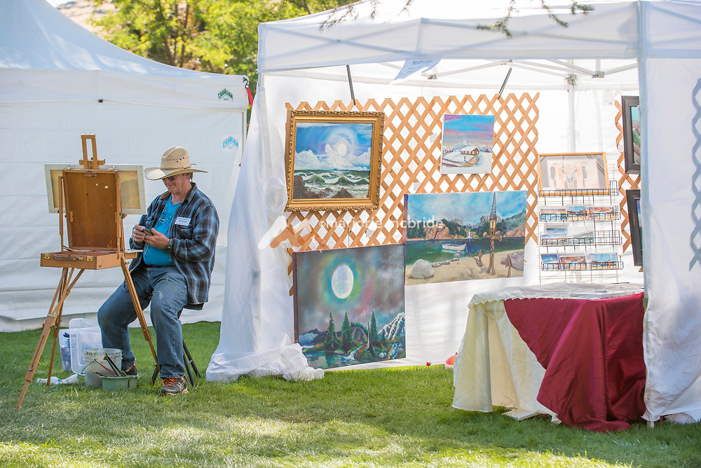 Painter Tex Archer looking at his phone during a break while working at his easel during the Thousand Springs Art Festival at Ritter Island near Hagerman, Idaho. VMR