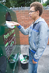 Teenage boy putting a plastic milk bottle into a recycling bank,
