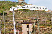 The Le Pavillon vineyard with the small house that has given it its name, a big sign with ermitage M Chapoutier and three people. The Hermitage vineyards on the hill behind the city Tain-l'Hermitage, on the steep sloping hill, stone terraced. Sometimes spelled Ermitage.  Domaine M Chapoutier, Tain l'Hermitage, Drome Drôme, France Europe