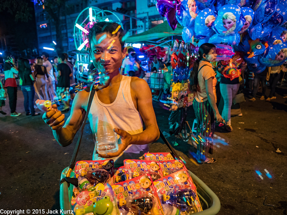 29 OCTOBER 2015 - YANGON, MYANMAR: Vendors sell bubble blowing toys during a street carnival in central Yangon. Electricity is scarce in Myanmar, especially in rural areas, and most traveling carnivals use human powered rides. Workers climb to the top of the Ferris Wheel and then pull it around getting it spinning. They do the same with Merry Go Rounds, but instead of climbing to the top they pull it around. The carnival coincided with the Thadingyut Festival, the Lighting Festival of Myanmar, which is held on the full moon day of the Burmese Lunar month of Thadingyut, October or November on the Gregorian calendar. The carnival featured food, rides and games.      PHOTO BY JACK KURTZ