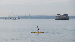 © Licensed to London News Pictures. 19/09/2016. Portsmouth, UK.  A man on a paddle board making the most of calm conditions and watching the installation works for new navigation light piles, which are being installed for the Queen Elizabeth Class Carriers in the Solent this morning, 19th September 2016. The weather is set to be cloudy with sunny intervals in the south east of England. Photo credit: Rob Arnold/LNP