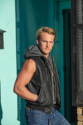 blond man with blue eyes in sleeveless leather jacket