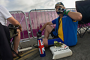 Spectators sips hot tea from a thermos flask on the first day of competition of the London 2012 Olympic 250km mens' road race starting from central London and passing the capital's famous landmarks before heading out into rural England to the gruelling Box Hill in the county of Surrey. Local southwest Londoners lined the route hoping for British favourite Mark Cavendish to win Team GB first medal but were eventually disappointed when Kazakhstan's Alexandre Vinokourov eventually won gold.