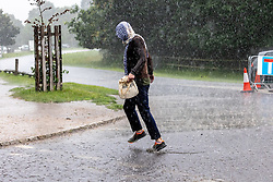 Licensed to London News Pictures. 12/07/2021. London, UK. A walker gets caught in torrential rain in Richmond Park, southwest London this afternoon with roads and pavements becoming quickly flooded as the Met Office issue yellow weather warnings for heavy rain and thunderstorms which may cause disruption to travel and flooding. However, sunshine and warm weather is predicted for the rest of the week with highs of 26c for the weekend.. Photo credit: Alex Lentati/LNP