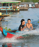Two young men in their motor boat in one of the floating village communities on the great Tonlé Sap lake, Cambodia