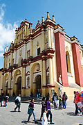 The Cathedral with people outside milling around and selling their wares, street scene, San Cristobal de las Casas, Chiapas, Mexico.