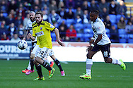 Brentfords' Alan Judge being chased by Bolton Wanderers' Neil Danns. Skybet football league championship match, Bolton Wanderers v Brentford at the Macron stadium in Bolton, Lancs on Saturday 25th October 2014.<br /> pic by Chris Stading, Andrew Orchard sports photography.