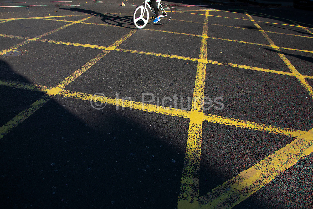 Cyclist passes through a yellow grid box junction in London, United Kingdom. A box junction is a road traffic control measure designed to prevent congestion and gridlock at junctions. The surface of the junction is typically marked with a criss-cross grid of diagonal painted lines or only two lines crossing each other in the box, and vehicles may not enter the area so marked unless their exit from the junction is clear, or they are intending to turn right and are prevented from doing so by oncoming traffic, or other vehicles on the box waiting to turn right.