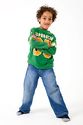 Little boy standing smiling in the studio,
