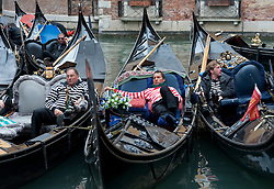 Gondoliers resting in ther gondolas on a canal in venice Italy