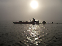 A kayak passing by in the misty backlight outside Spitzbergen