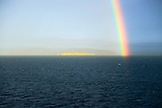 Seascape view of spectrum colours in rainbow over sea and island, Norway