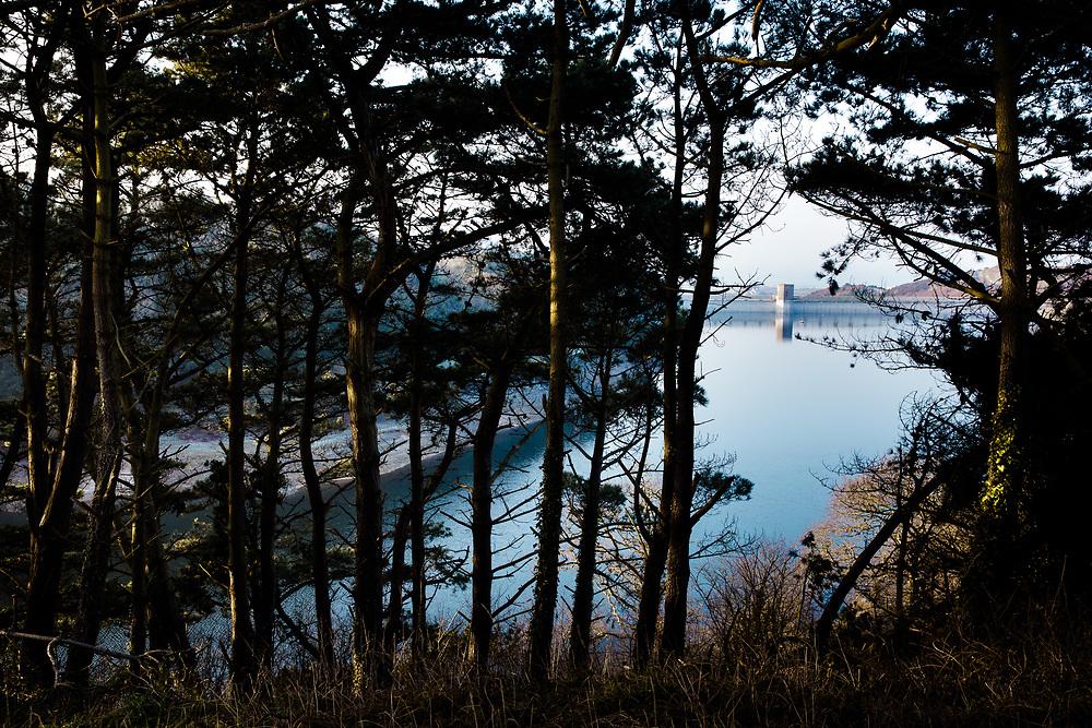 Calm, reflective, glassy water at Val de la Mar Reservoir in Jersey, Channel Islands