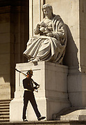 A ceremonial soldier stands guard outside the Palacio de Sao Bento, the Portuguese parliament building while in session, Estrela district, Lisbon. Walking beneath a giant stone statue, the guard has a rifle with fixed bayonet shouldered. São Bento Palace (Palace of Saint Benedict) is the home of the Assembly of the Republic, the Portuguese parliament. Its main façade has been altered numerous times since its 16th-century original.