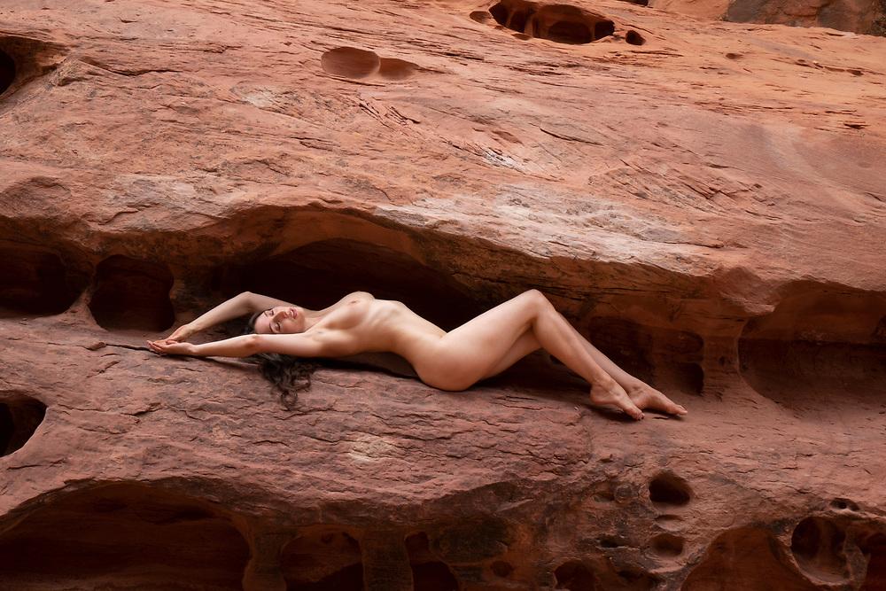 Nude woman reclining in a crevice of Crack Canyon, San Rafael Reef, Utah