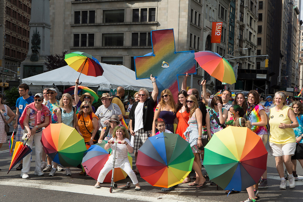 Marchers bearing a huge rainbow cross pose for a photo.
