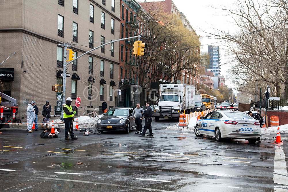 A male cyclist lies on the road talking on his phone after falling off his bike which crashed with the black VW car on East Houston Street in Lower East Side, New York City, New York, Unites States of America. An NYPD officer walks towards him, while the male drive of the car stands and watches. A workman with a STOP sign controls the traffic.