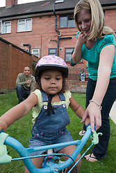Mother and father teaching their daughter to ride a bike.