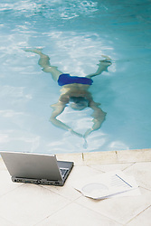 Dec. 05, 2012 - Man in swimming pool with computer (Credit Image: © Image Source/ZUMAPRESS.com)