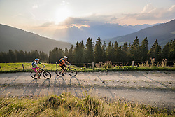 Elevated view of mountain bikers riding on dirt road during sunset, Zillertal, Tyrol, Austria
