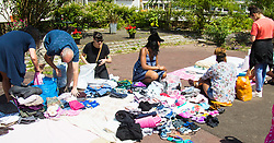 London, June 14th 2017. As fire rages through a residential tower block, Grenfell Tower, in Kensington, West London, local residents show their generosity as well-wishers pour into the Maxilla Social Club with clothing, food, water and blankets for the residents of the block who will have lost everything. PICTURED: Volunteers categorise clothing donations by kind and size.